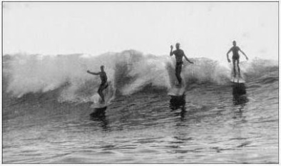 Buzzy Bent (left) rides a balsa board shaped by Joe Quigg, as Dempsey Holder (center) and Bobby Ekstrom share the same wave in 1949.